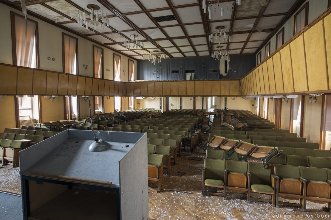 Adam X Urbex Nazi School Partishule N DDR Horsaal Germany Urban Exploration Decay Lost Abandoned auditorium ceiling seats chairs view from the stage lectern