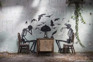 Skeletons table overgrown ivy lampshade bats squatters Usine Skeleton factory ROA Klaas Van der Linden Adam X Urbex Urban Exploration Belgium Access 2017 Abandoned decay lost forgotten derelict location creepy haunting eerie